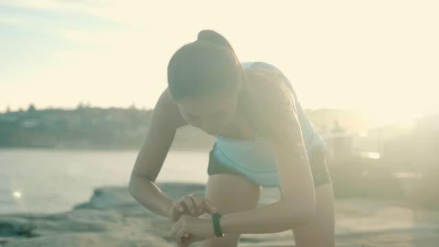 beautiful asian runner checking smart watch - носимый компьютер стоковые видео и кадры b-roll