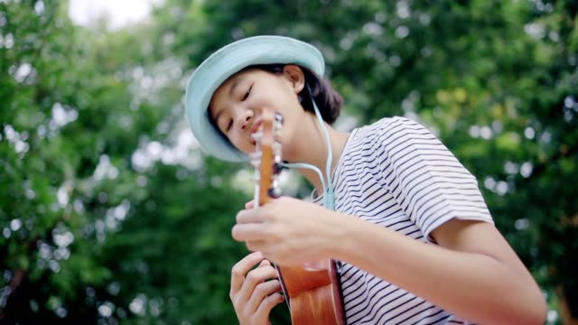 Beautiful Asian teenage girl playing at ukulele in the park, Slow motion