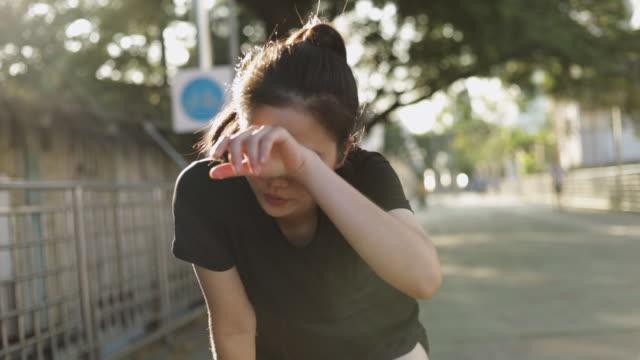 vídeos y material grabado en eventos de stock de hermosa mujer asiática atleta corriendo descansando agotado después de un ejercicio de entrenamiento cardiovascular en la puesta de sol de la ciudad urbana. jogging estilo de vida saludable. chica corredora usando auriculares escuchando música. - training