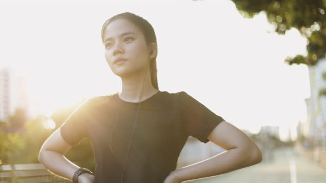 vídeos de stock e filmes b-roll de beautiful asian woman athlete running resting exhausted after a cardio workout exercise in the urban city sunset. jogging lifestyle healthy. girl runner wearing earphones listening to music. - training