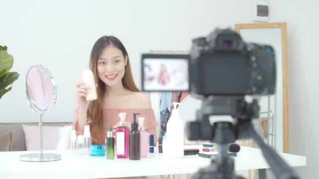 美しいアジアの女性ブロガーは、化粧品を作り、使用する方法を示しています。自宅でvlogビデオライブストリーミングを記録するためにカメラの前に。ソーシャルメディアのコンセプトに関 - スタジオ 日本人点の映像素材/bロール