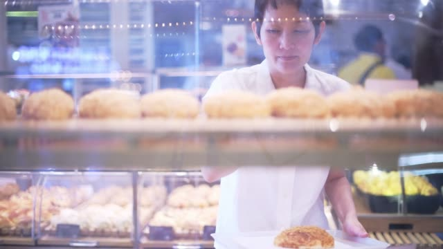 Beautiful Asian woman chooses bread in the bakery department in the supermarket. Healthy eating concept Beautiful Asian woman chooses bread in the bakery department in the supermarket. Healthy eating concept market retail space stock videos & royalty-free footage