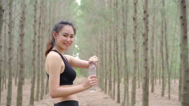 美しいアジアの女性ランナー運動心肺機能トレーニングや汗回復リフレッシュメント アクティブな健康的なライフ スタイル、山ヒルの損失の後のリラックスの森自然でクールな水のボトルを飲みます。 - 女性選手点の映像素材/bロール