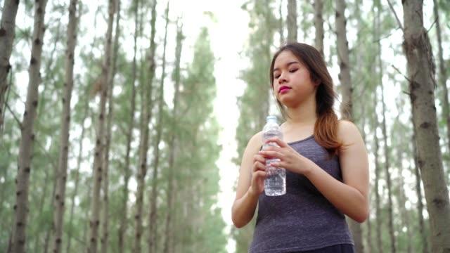 リラックスして休んで回復後アクティブなスポーツの森自然の中の美しいアジアの女性の飲料水ボトル疲れて運動心臓健康的なライフ スタイルになります。 - 女性選手点の映像素材/bロール
