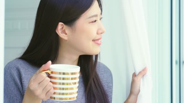beautiful asian woman enjoy morning time with hot drink in bedroom with window light