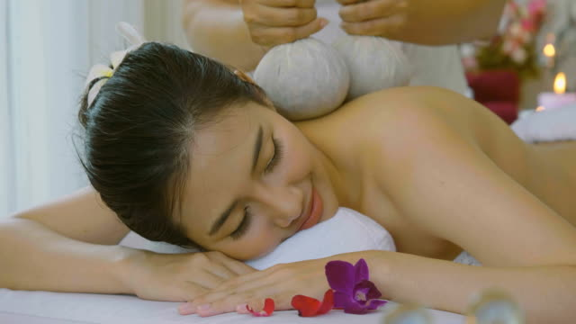 ds : beautiful asian woman enjoying thai herbal compress massage treatment - alternative medicine stock videos and b-roll footage