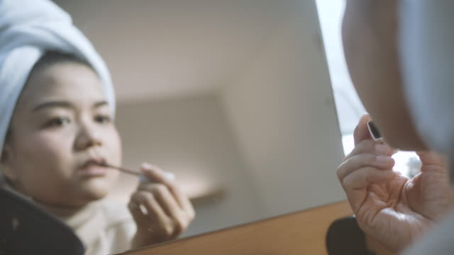 Beautiful asian woman  is doing her make up and use cosmetics In front of mirror at home for her beauty daily routine.