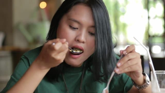 vidéos et rushes de belle femme asiatique est de manger au restaurant déjeuner de plat principal - fourchette
