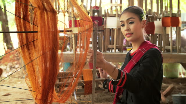 Beautiful asian woman is weaving cotton with a traditional tools. video