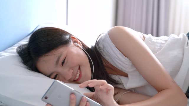 ベッドで幸せな笑顔のスマートフォンで音楽を聴く美しいアジアの女性は、寝室で毛布の下に横たわって快適な休息ホテルの人々のライフスタイルスローモーション4k解像度。 - スマホ ベッド点の映像素材/bロール