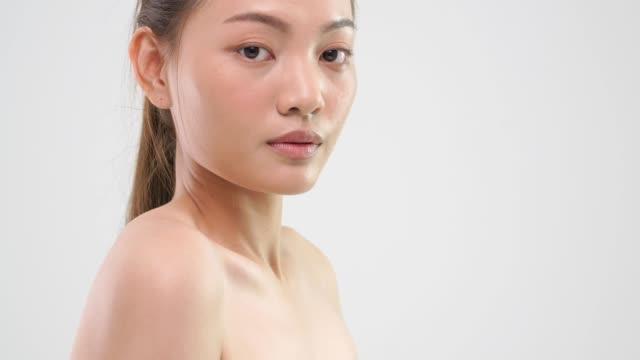 (tilt up) beautiful asian woman looking at camera in studio shot. - viziarsi video stock e b–roll
