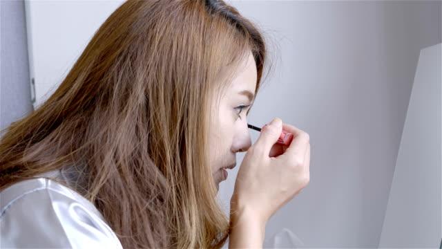 美しいアジアの女性は家庭で朝の寝室の鏡の前でメイクアップします。ビューティー コンセプト - まつげ点の映像素材/bロール