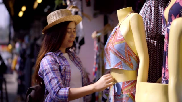 Beautiful Asian woman shopping on the Chatuchak weekend market in the Thailand vacation choosing choosing new clothes, looking through hangers with different casual colorful garments on hangers, Shopping concept  for herself.Business concept. video