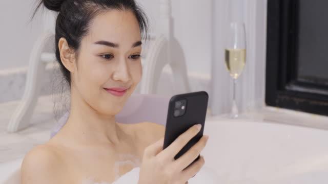 バスルームでバブルバスを取って美しいアジアの女性。彼女はお風呂に入りながら幸せな感情でスマートフォンを使用しています。 - バス点の映像素材/bロール