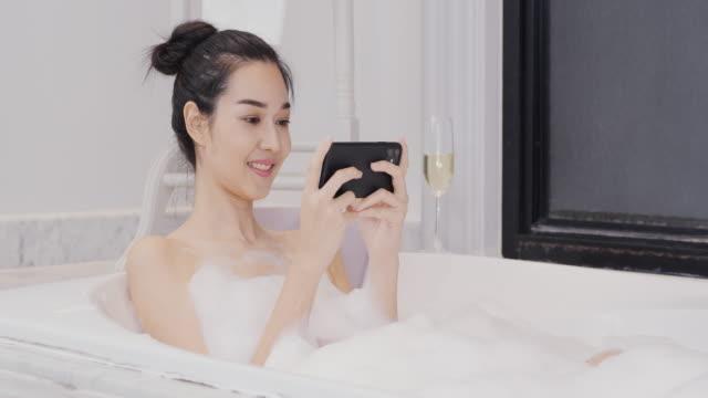 vacker asiatisk kvinna tar ett bubbelbad i badrummet. hon använder smartphone med glada känslor medan du tar bad. - japanese bath woman bildbanksvideor och videomaterial från bakom kulisserna