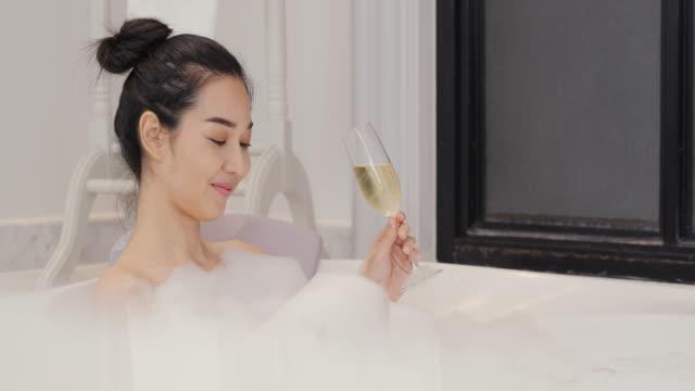 vacker asiatisk kvinna tar ett bubbelbad i badrummet. hon dricker vin med glada känslor medan du tar bad. - japanese bath woman bildbanksvideor och videomaterial från bakom kulisserna