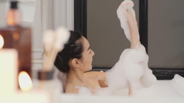 バスルームでバブルバスを取って美しいアジアの女性。彼女は幸せな感情で自分自身を掃除します。 - バス点の映像素材/bロール