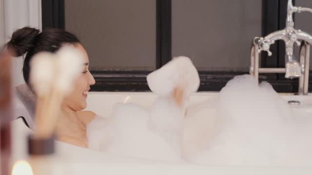 vacker asiatisk kvinna tar ett bubbelbad i badrummet. hon städar sig med glada känslor. - japanese bath woman bildbanksvideor och videomaterial från bakom kulisserna