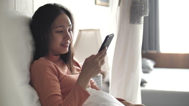 美しいアジアの女性の自宅のベッドで携帯電話を使用して - 電話を使う点の映像素材/bロール
