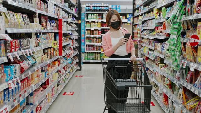 vídeos y material grabado en eventos de stock de hermosa mujer asiática usando una máscara protectora de la cara de compras y el uso de teléfono inteligente en un supermercado - snack aisle