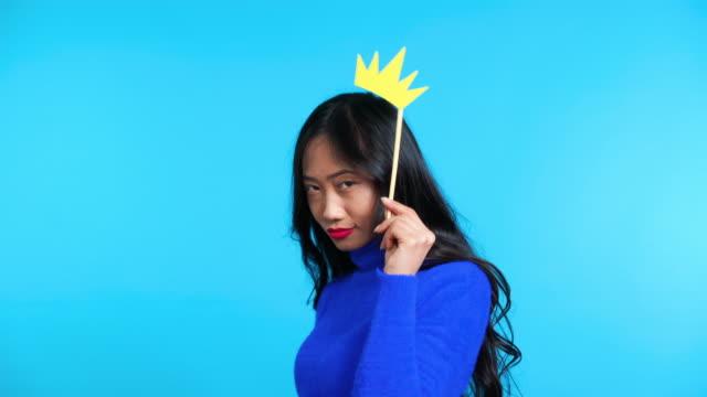 vidéos et rushes de belle femme asiatique avec la couronne de papier sur le bâton posant sur le fond bleu - couronne reine