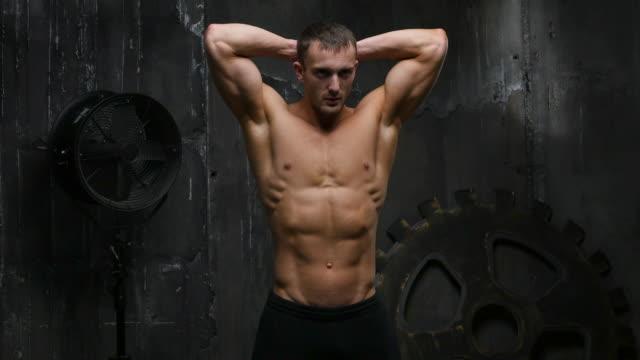 wunderschöne athlet zeigt muskeln im studio - nackter oberkörper stock-videos und b-roll-filmmaterial
