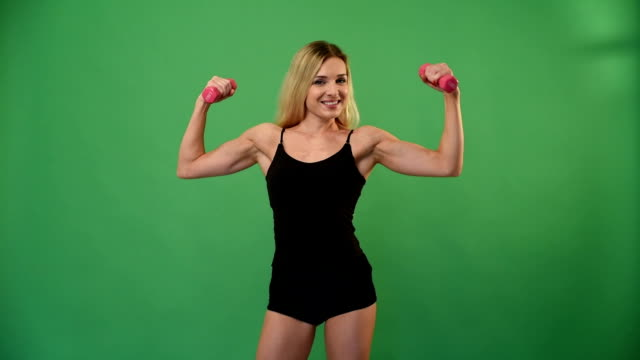 beautiful athletic blonde with dumbbells on green background - weights stock videos & royalty-free footage
