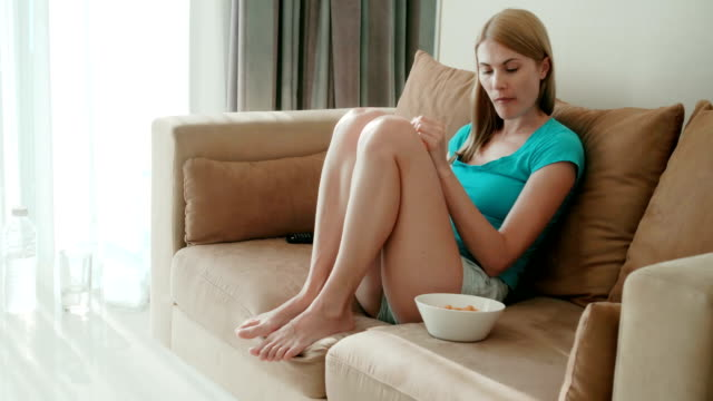 beautiful attractive woman sitting on sofa and watching movie. eating chips from white bowl - leccare video stock e b–roll