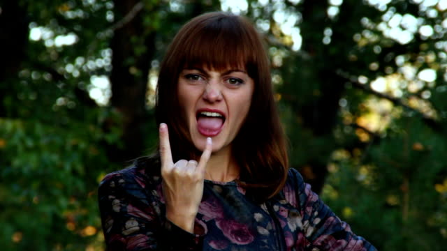 Beautiful attractive young girl shows tongue and Gesture Rockers video