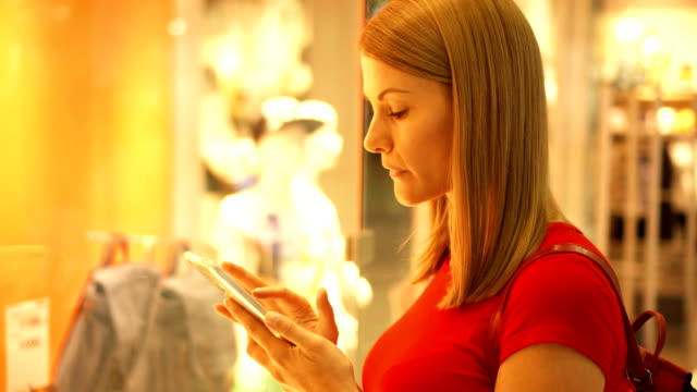 Beautiful attractive young woman near window shop in mall. Checking store prices on her smartphone