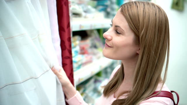 Beautiful attractive young woman selects blinds on the shelves in the store. Consumerism concept video