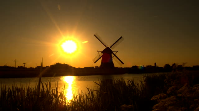 Beautiful authentic old windmill on the river bank at beautiful golden sunrise video