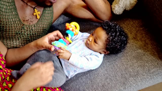 beautiful baby playing with toys on the couch