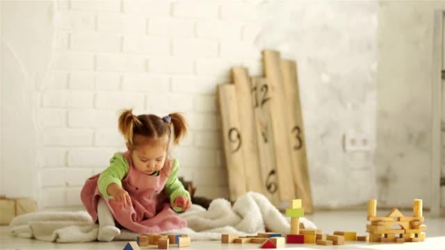 stockvideo's en b-roll-footage met een prachtige baby speelt op de verdieping met houten kubussen. educatief speelgoed. voorschoolse educatie. kleuterschool - baby toy