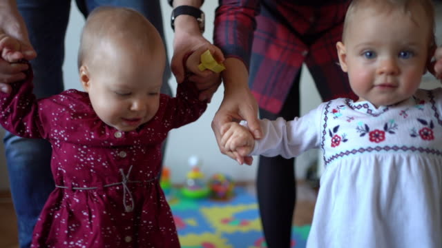 beautiful baby twins learn to walk - gemelle video stock e b–roll