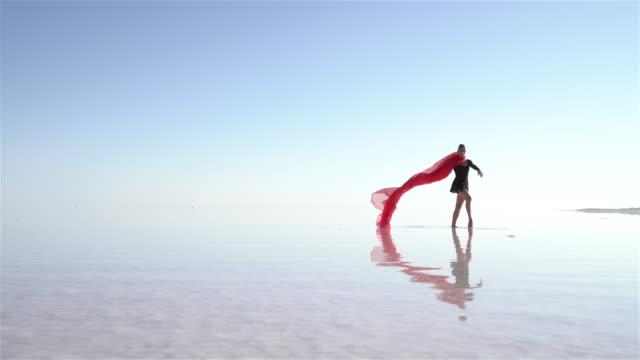 Beautiful ballerina dancing on the lake with red tulles Salt Lake Concept. tulle netting stock videos & royalty-free footage