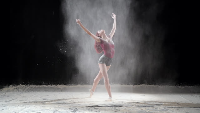 Beautiful ballerina dancing with powder snow at studio. Slow motion video