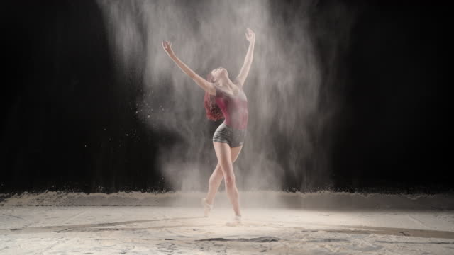 Beautiful ballerina dancing with powder snow at studio. Slow motion dance with powder concept in studio ballet dancer stock videos & royalty-free footage