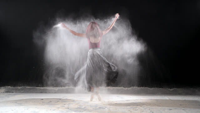 Beautiful ballerina dancing with powder snow at studio. video