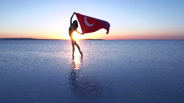 Beautiful ballerina holding a Turkish flag on the water. A windy day. video
