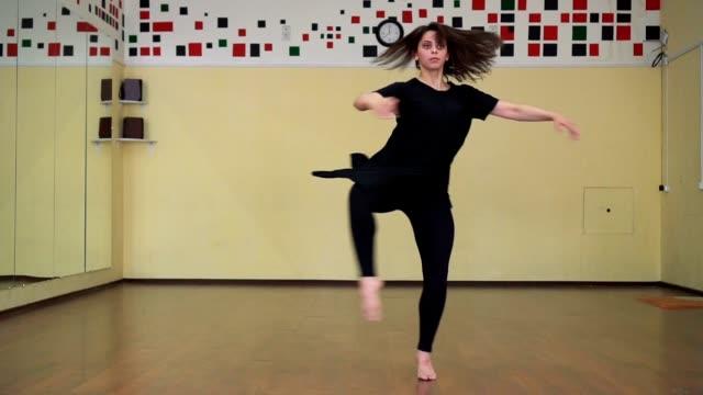 vackra ballerina i svart klänning utför piruetter i studion - gympingdräkt bildbanksvideor och videomaterial från bakom kulisserna