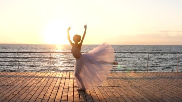 vackra ballerina i vitt tutu dans, hoppa på trägolvet nära havet eller ocean. solen skiner på bakgrunden - piruett bildbanksvideor och videomaterial från bakom kulisserna