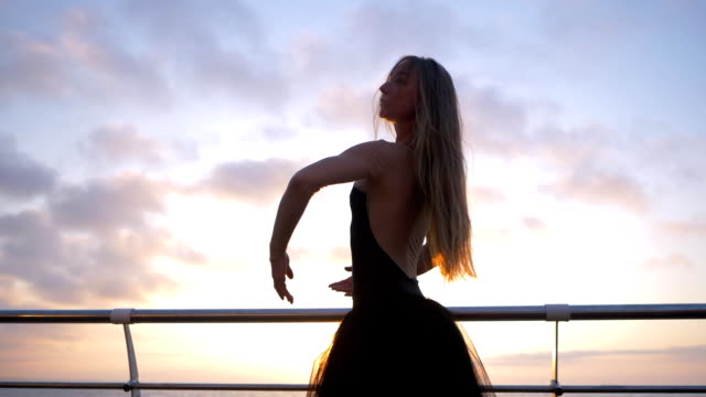 slow motion. beautiful ballerina performing pirouette. blonde woman in black ballet tutu on embankment above ocean or sea beach at sunrise. female dancing with arms - mani sui fianchi video stock e b–roll