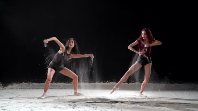 Beautiful ballerinas dancing with powder snow at studio. Slow motion video