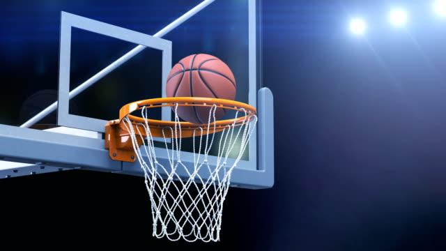 vídeos y material grabado en eventos de stock de hermosa baloncesto bola golpea canasta red lenta cerca cámara fly. bola vuela girando en aro de baloncesto con luces de estadio azul. concepto del deporte de animación en 3d - basketball hoop