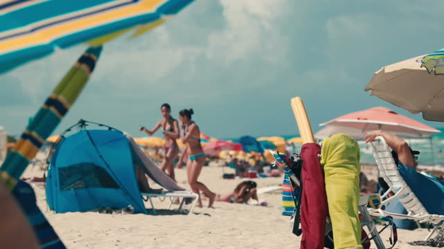 Beautiful beach with umbrellas and people hanging out video