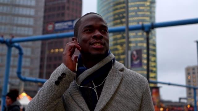 Beautiful black businessman in winter coat listening to music