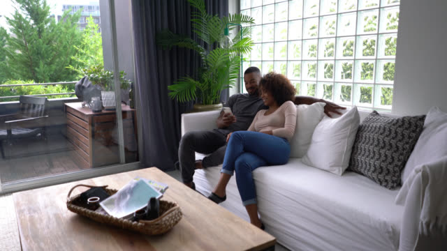 vídeos de stock e filmes b-roll de beautiful black couple at home relaxing watching something on smartphone laughing - aproximar imagem