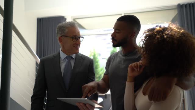 vídeos y material grabado en eventos de stock de hermosa pareja negro mirando una propiedad mientras que el agente de bienes raíces está mostrando algo de tableta - propiedad inmobiliaria