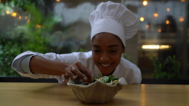 güzel siyah kadın şef bir salata için bir son dokunuş ekleyerek kamera gülümseyen karşı karşıya - chef stok videoları ve detay görüntü çekimi